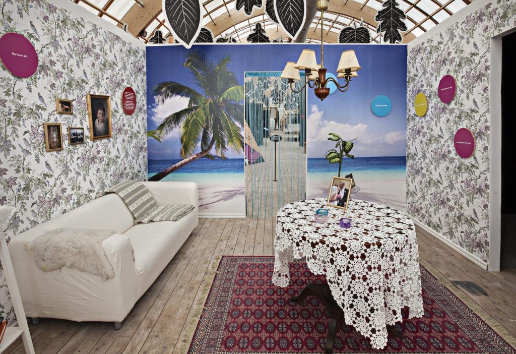 Bild på ett möblerat rum med en vit soffa, bord med vit duk på. Ett foto står på bordet. Under bordet finns en rödmönstrad matta. Väggarna har en blommönstrad tapet. Fondväggen har en tapet föreställande en sandstrand med en hav och palm. I taket hänger en lampa.