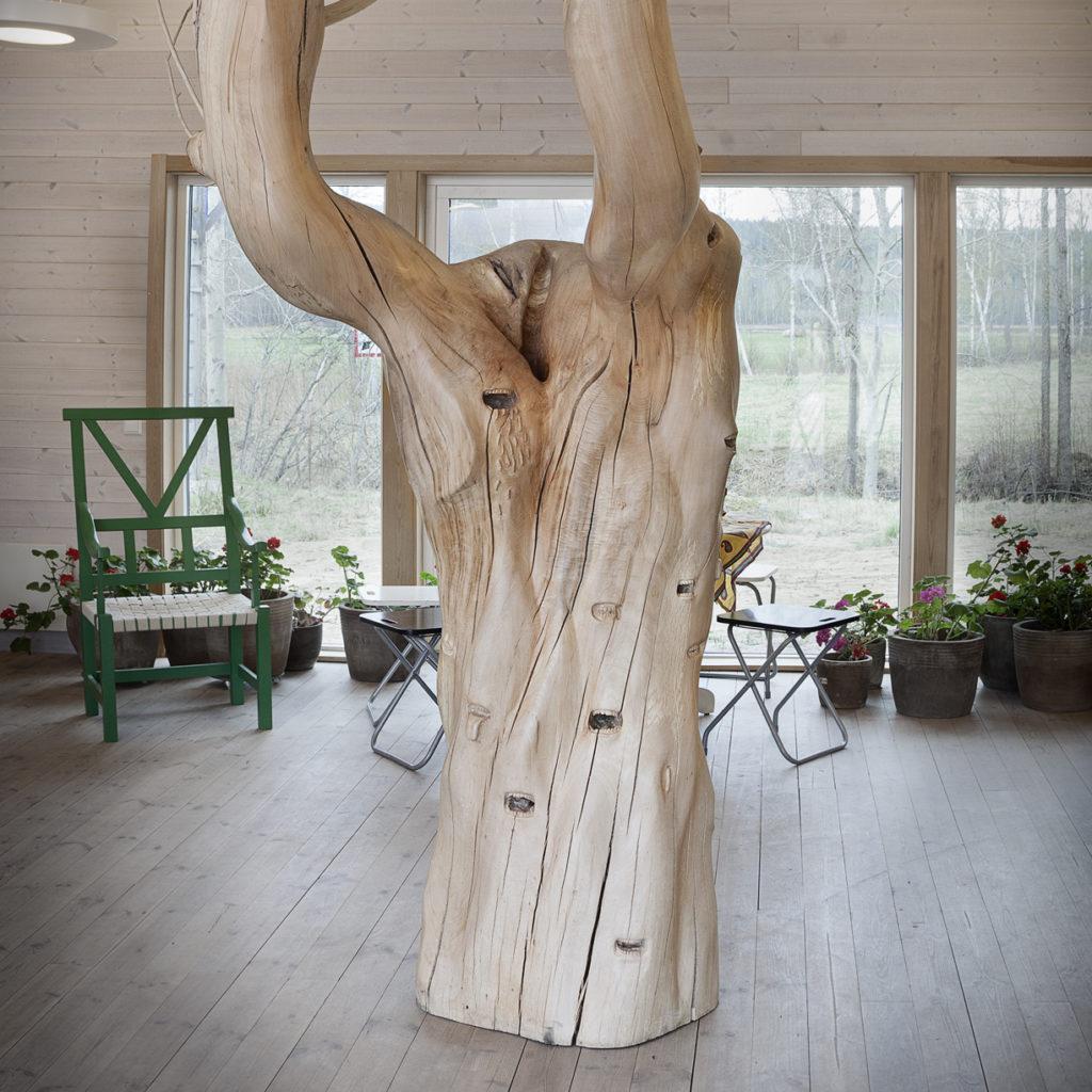 Bild på en stor träfigur stående i mitten. Bakom finns blommor och en grön stol.