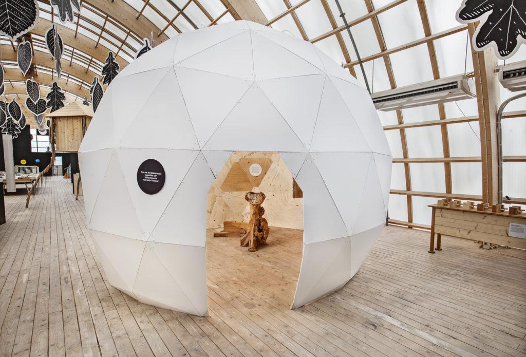 Bild på en vit stor rund sfär med träfigurer inuti.