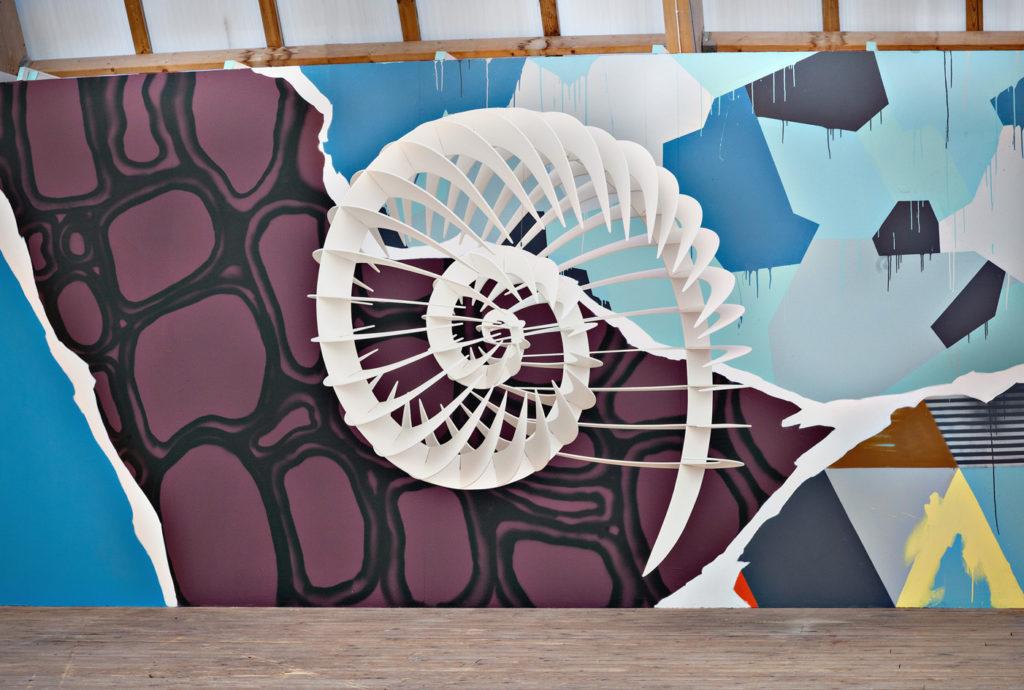 Bild på en färgrik vägg med en vit träfigur. Konstverk av Gunilla Poi