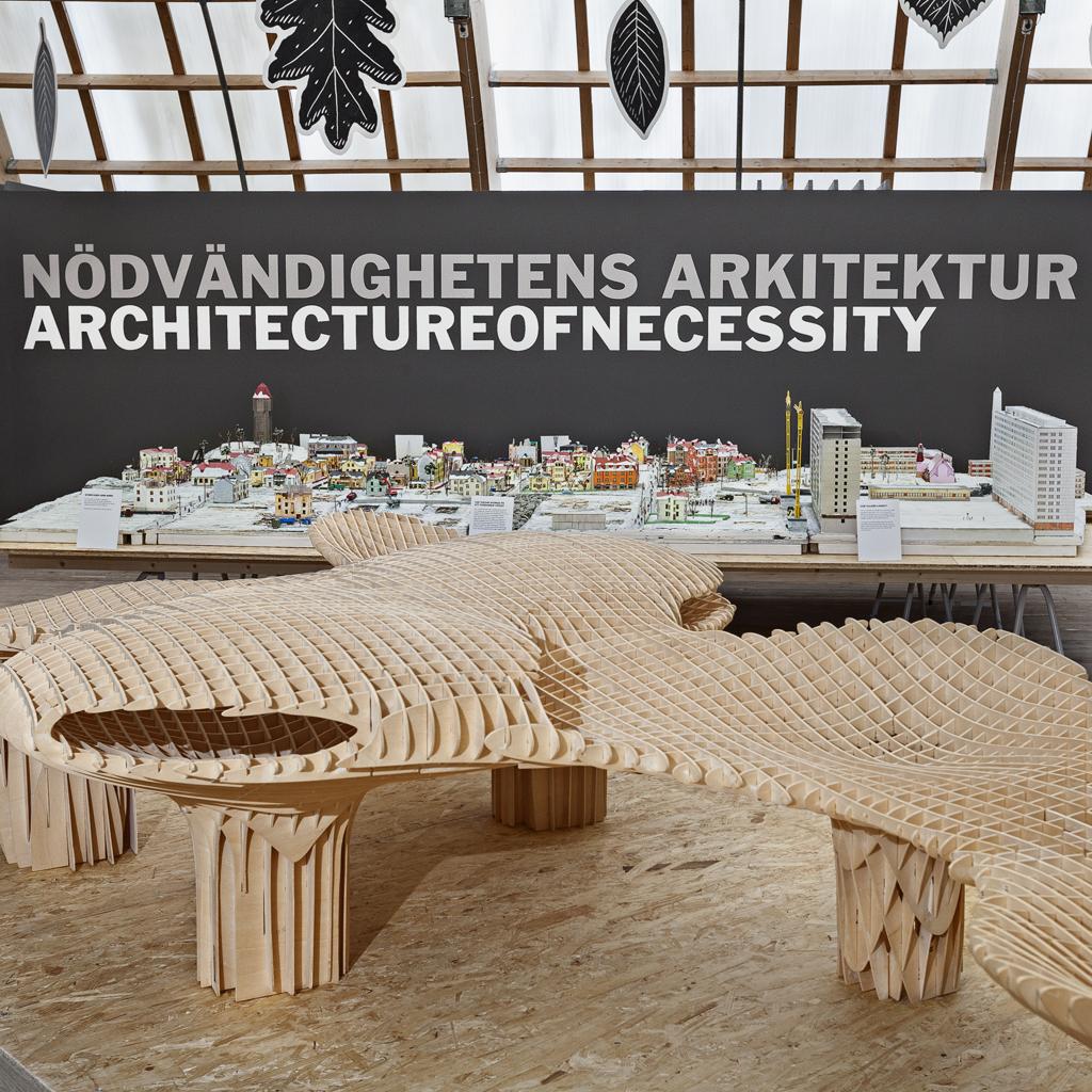 Bild på en trämodell framför vägg med Nödvändighetens arkitektur