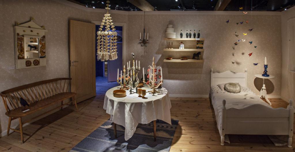 Bild på ett möblerat rum med slöjd samt en säng, bänk, bord med saker på. Finns även en hylla på väggen och fåglar hängande från taket.