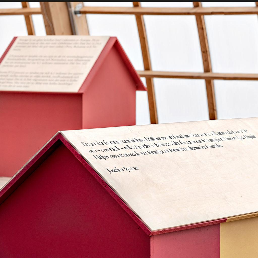 Bild på två röda trähus. Text finns på taken.