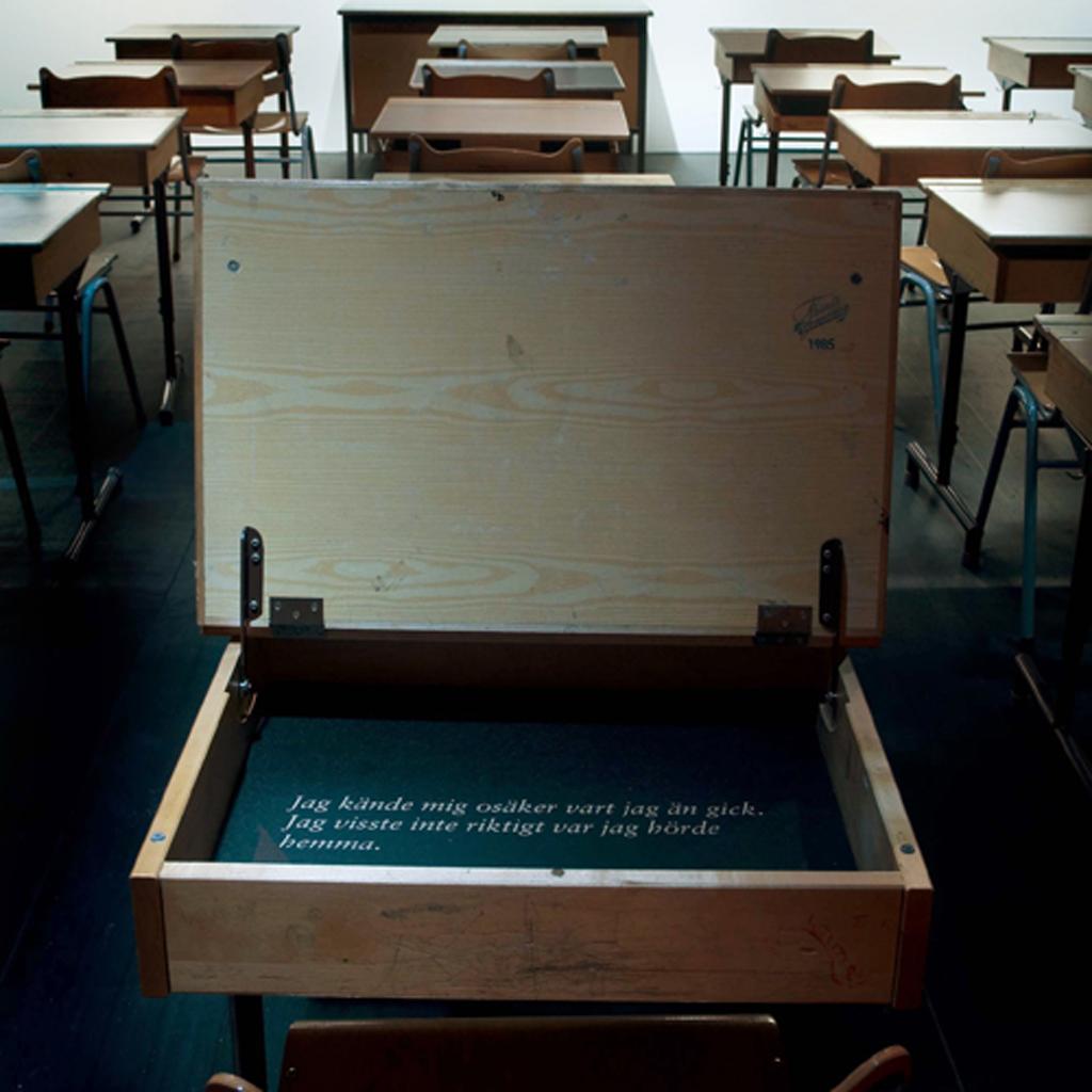 Bild på ett klassrum med skolbänkar. En bänk har locket öppet. I bänken står det en vit text.